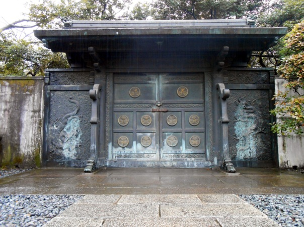 The gate still exists. Not sure if they moved it, but my gut instinct says it's in the same place as it originally was. Today it is the entrance to the Tokugawa Cemetery, which houses the graves of the other shoguns enshrined at Zojo-ji. My guess is that the area is original tamaya of Ienobu.