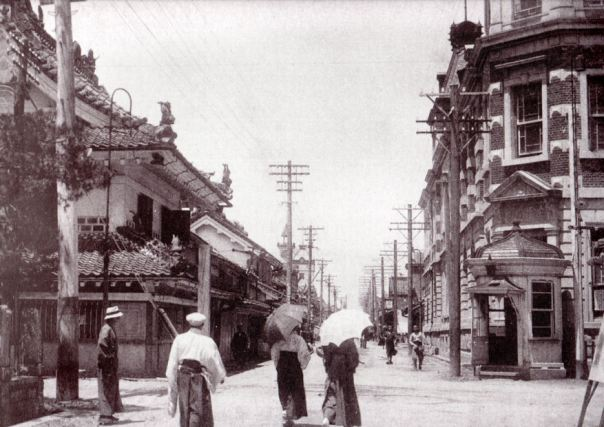 "A random photo of a Taisho Period intersection. Modern Japanese cities are generally huddled together close knit towns and so intersections have always been very important. This photo includes a ""police box"" which emphasizes the importance and centrality of this particular location."
