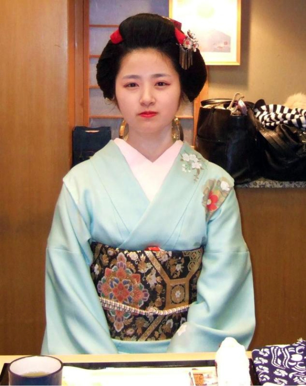 Tomochiyo, a young geisha who debuted in Kagurazaka in 2010. She's dressed casually in this informal shot, but I like the photo because it looks like she isn't wearing a wig, but is using her natural hair. I think she's pretty cute. How about you?